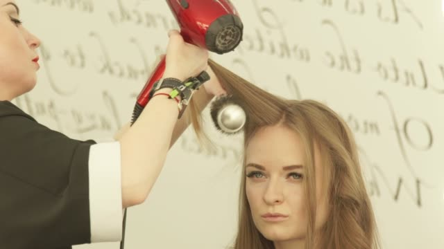 Blonde-woman-during-hairstyling-long-hair-with-dryer-and-hairbrush-in-hairdressing-salon-Close-up-haircutter-drying-woman-hair-with-dryer-and-comb-after-washing-and-cutting