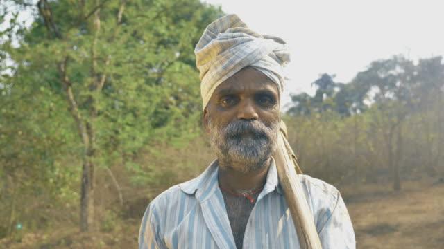 Un-agricultor-hombre-de-pie-en-su-tierra-agrícola-rodeado-de-árboles-con-pico-