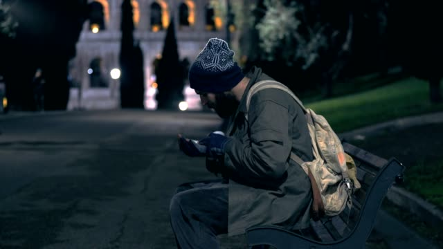 Lonely-homeless-sit-on-bench-at-night-cheking-his-alms