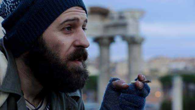 close-up-on-Pensive-homeless-thinks-and-smoking-a-cigarette-taking-a-decision