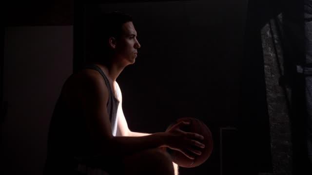 Jugador-de-baloncesto-sentado-y-esperando-el-juego-empezar-va-a-zona-de-juegos