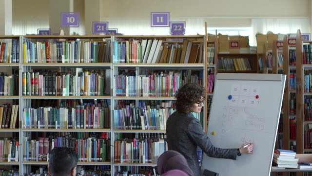 Profesora-explicando-la-palabra-en-inglés-para-estudiantes-migrantes