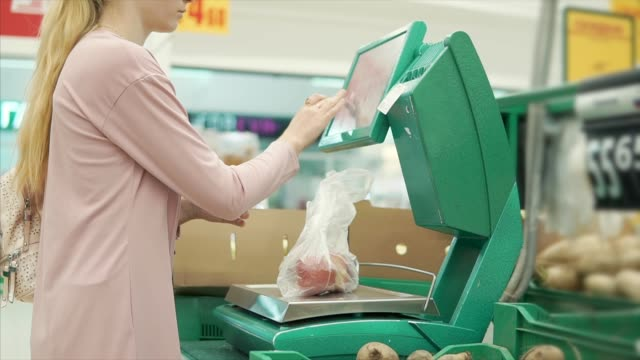 Female-shopper-is-weighing-vegetables-on-a-scale-in-a-supermarket