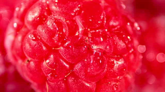 Macro-shot-drops-of-clear-transparent-water-falling-on-raspberry