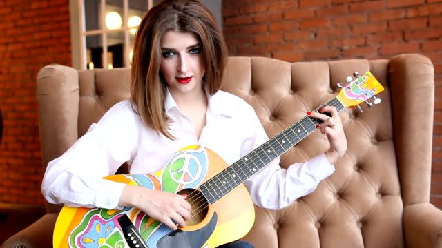 Woman-in-a-white-shirt-plays-guitar-in-hippie-style