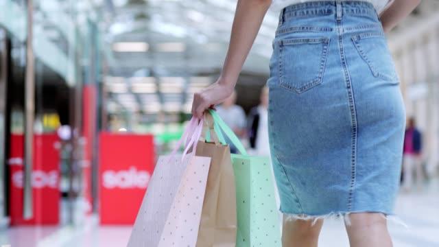 Folgen-Sie-Schuss-Rückansicht-unkenntlich-Frau-in-Denim-Bleistiftrock-in-Shopping-Mall-zu-Fuß-mit-Haufen-von-Einkaufstüten-in-der-hand