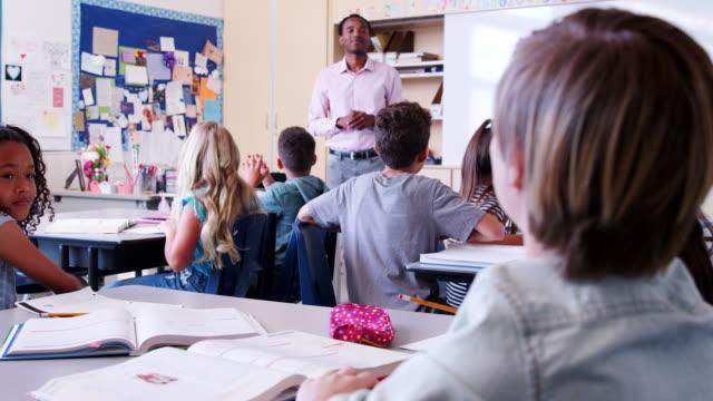 Escuela-primaria-niños-levantan-las-manos-al-maestro