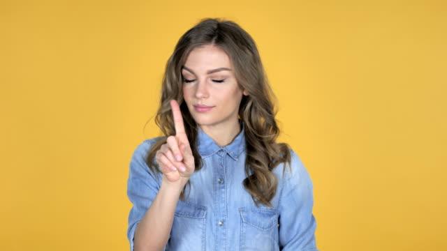 Chica-joven-agitando-el-dedo-para-rechazar-aislado-sobre-fondo-amarillo