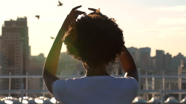 Junge-Afro-amerikanische-Frau-auf-Dach-sitzt-und-meditiert,-beobachtete-Stadtbild