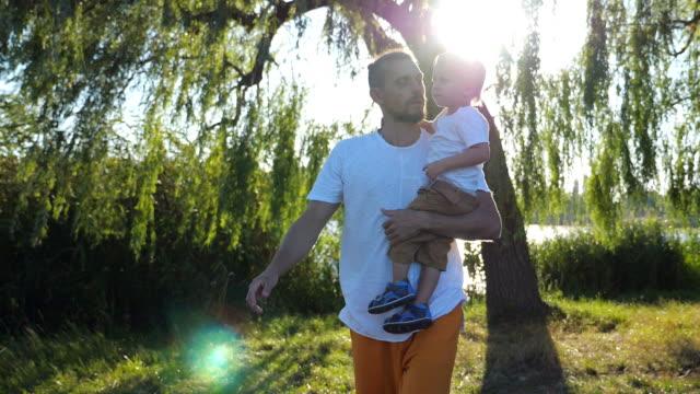 Papá-joven-sosteniendo-a-su-pequeño-hijo-en-las-manos-y-caminando-en-el-parque-de-verano-en-un-día-soleado-Familia-feliz-pasar-tiempo-juntos-y-disfrutar-de-la-naturaleza-Hermoso-paisaje-en-el-fondo-Lenta-de-cerca