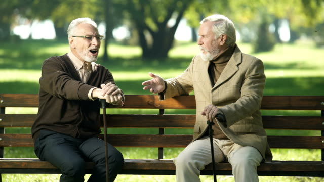 Senior-man-suffering-age-related-Alzheimer-disease-old-friends-talking-in-park