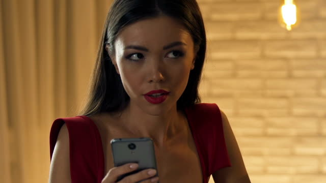 Bored-woman-using-smartphone-on-date-irritated-with-annoying-man-closeup