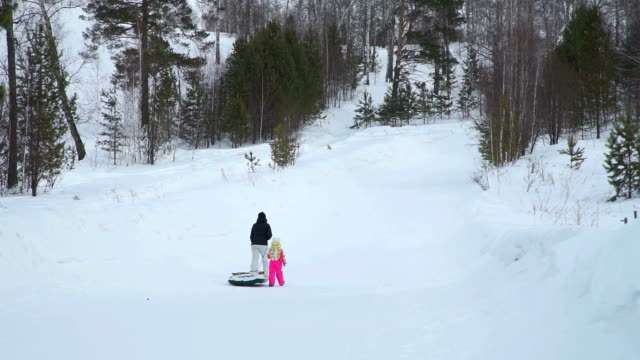 Mom-and-Daughter-Climbing-a-Hill-with-Snow-Tube