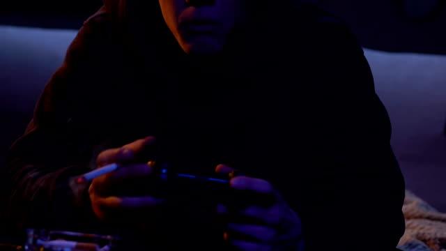 Adolescente-sin-trabajo-que-juega-activamente-videojuego-usando-gamepad-problema-de-desempleo