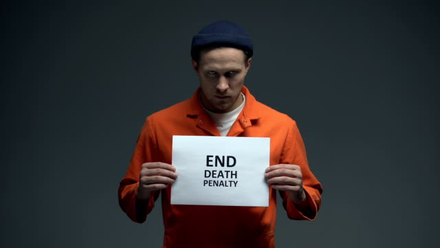 Caucasian-male-prisoner-holding-End-death-penalty-sign-in-cell-asking-for-help