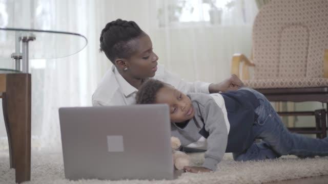 Mujer-afroamericana-con-su-lindo-hijo-mirando-la-Laptop-