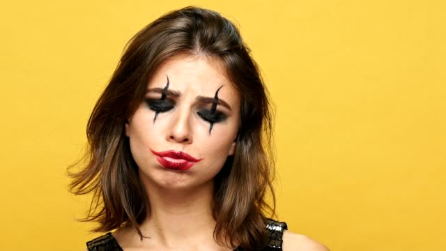 Upset-brunette-lady-with-creepy-make-up-for-halloween-looking-camera-isolated-over-yellow