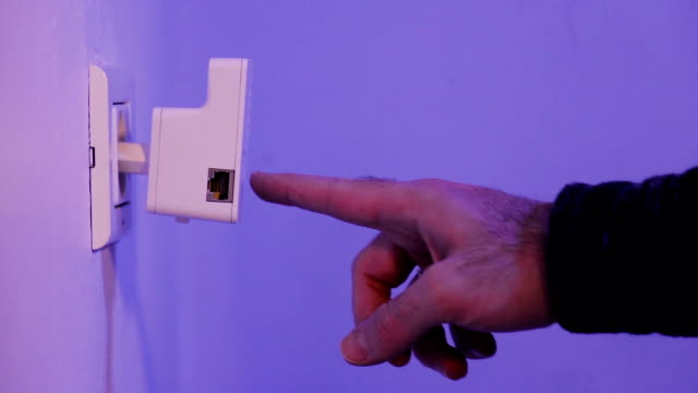 Man-press-with-his-finger-on-WPS-button-on-WiFi-repeater-which-is-in-electrical-socket-on-the-wall