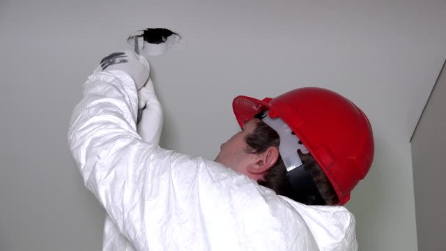 man-making-plasterboard-ceiling-holes-for-lighting-installation