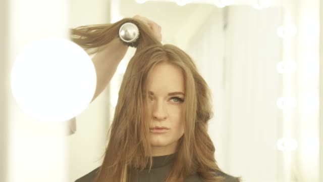 Young-woman-during-drying-long-hair-with-dryer-and-hairbrush-front-mirror-in-hairdressing-salon-Close-up-hairstylist-drying-woman-hair-with-dryer-and-comb-in-beauty-salon