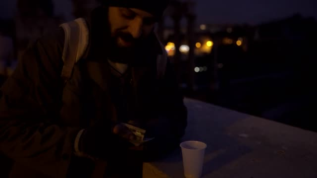 Smiling-homeless-counting-his-money-in-the-night--misery-joy-money