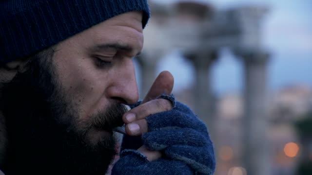 profile-of-lonely-homeless-lighting-cigarette