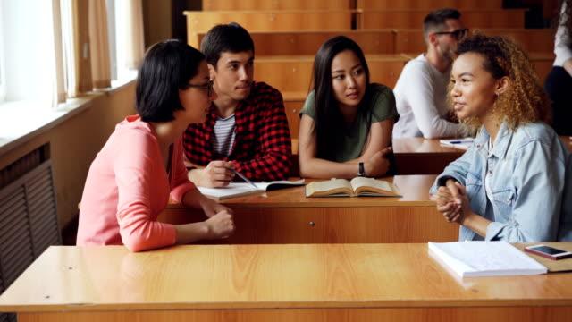 Students-are-discussing-team-project-sitting-at-desks-in-university-girls-and-boys-are-talking-notebooks-pens-and-smartphones-are-visible-Teamwork-and-communication-concept-