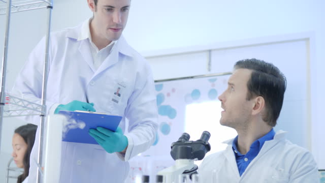 Team-of-Medical-Research-Scientists-Looking-at-Substance-under-Microscope-Writing-Down-Analysis-Results-In-A-Modern-Laboratory