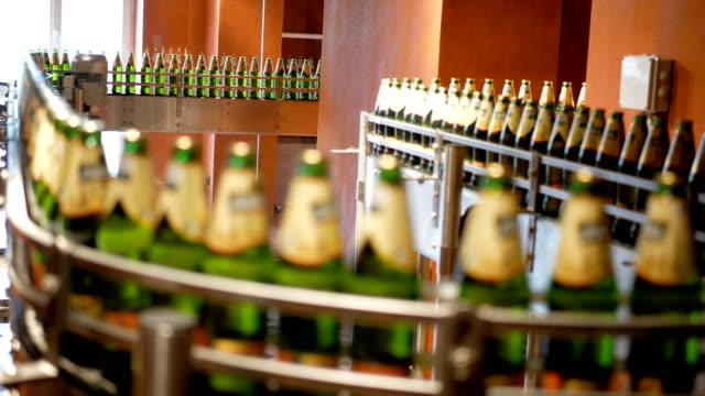 Große-Anzahl-von-Glasflaschen-mit-Bier-bewegen-sich-entlang-der-Förderer-Geringe-Alkohol-Produktion-Getränke-werden-zum-Verzehr-bereit-Betriebseinrichtung-bei-der-Arbeit-Das-fertige-Produkt-wird-zu-einem-anderen-Zeitpunkt-verschoben-Fabrikautomatio