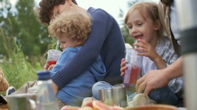 Children-Drinking-Juice-on-Picnic-with-Parents