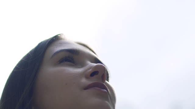 Mujer-calma-apacible-mirada-al-cielo-sueño-niña-valiente-mirada-hacia-futuro-lento
