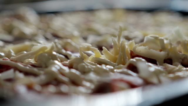 Cheese-falls-on-the-sauce-and-salami-delicious-and-appetizing-pizza-close-up-The-concept-of-pizza