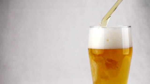 Cerveza-de-cerveza-dorada-ligera-está-vertiendo-en-vidrio-sobre-fondo-blanco-Cámara-lenta