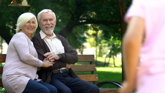 Old-couple-sitting-on-bench-and-happily-watching-their-grandchildren-having-fun