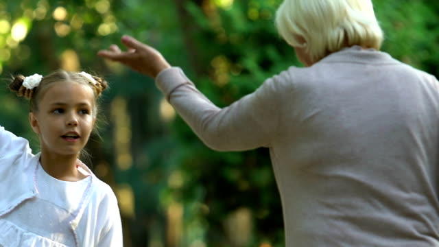 Little-active-girl-emotionally-talking-to-granny-while-walking-in-park-family