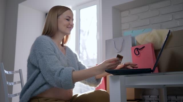 Pago-por-Internet-hermosa-mujer-expectante-con-tarjeta-de-crédito-utiliza-el-ordenador-portátil-para-compras-en-línea-en-Internet