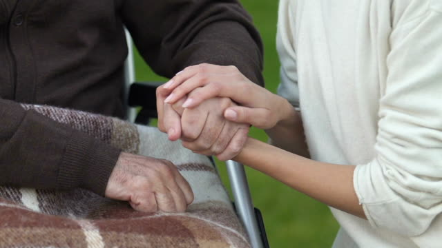 Daughter-stroking-hand-of-disabled-father-supporting-during-treatment-period