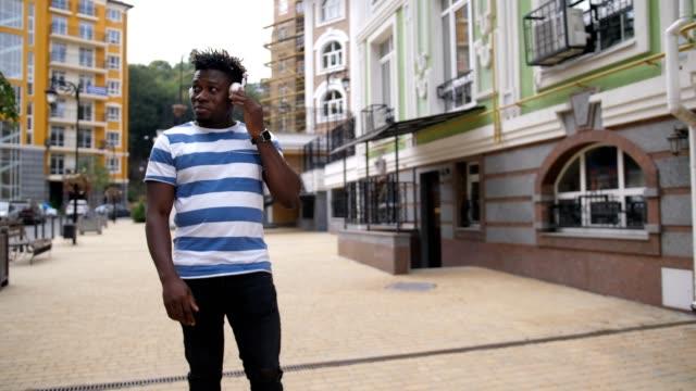 Joyful-black-man-enjoying-music-on-city-street