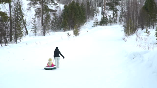 Mother-and-Daughter-Pulling-a-Snow-Tube-to-a-Hill