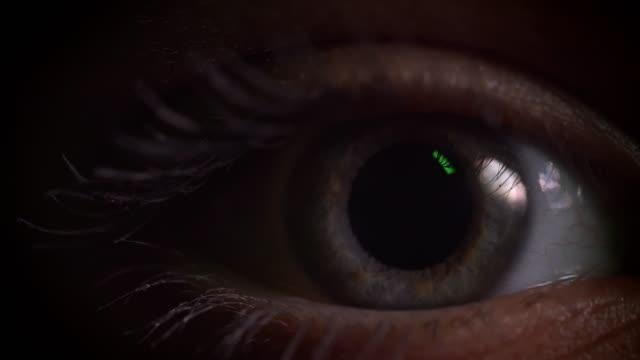 Toma-de-primer-plano-de-ojos-grises-parpadeando-con-reflejo-de-la-lámpara-verde-en-él-en-completa-oscuridad-