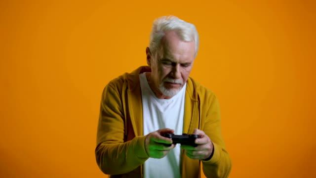 Hombre-de-la-tercera-edad-emocional-emocional-con-joystick-jugando-videojuego-molesto-con-el-resultado-redondo