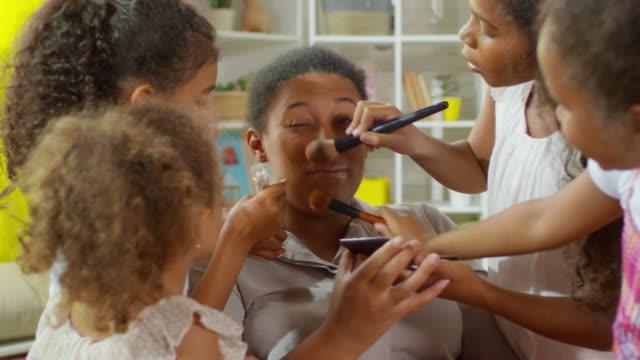 Mädchen-die-Make-up-auf-das-Gesicht-der-Mutter-anwenden