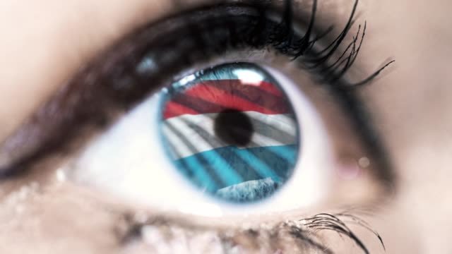 woman-blue-eye-in-close-up-with-the-flag-of-Luxembourg-in-iris-with-wind-motion-video-concept