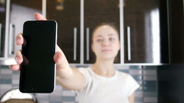 young-woman-showing-smart-phone-screen-on-the-kitchen