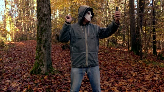 Man-with-scary-Halloween-mask-take-selfies-on-phone