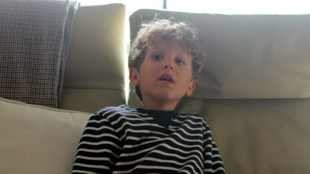 Child-face-trying-to-watch-television-screen-in-4K-Young-boy-seated-in-sofa-starring-and-wanting-to-see-something-behind-viewer