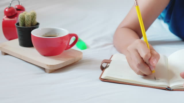 Woman-hands-with-pen-writing-notebook-on-bedroom-4k-Footage-with-dolly-shot