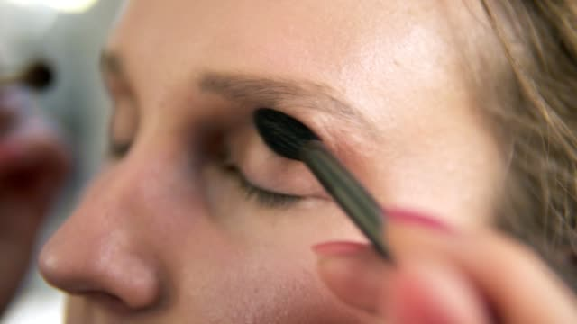 Extremely-close-of-a-young-woman-s-face-Make-up-artist-putting-on-nude-eyeshadows-using-two-brushes-at-the-same-time