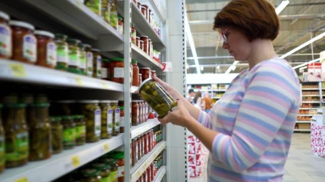 Caucasian-woman-near-shop-shelves-choosing-marinade-cucumbers-in-grocery-market