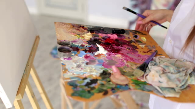 Close-up-of-the-woman-holding-a-large-palette-of-paints-and-brushes-for-drawing-